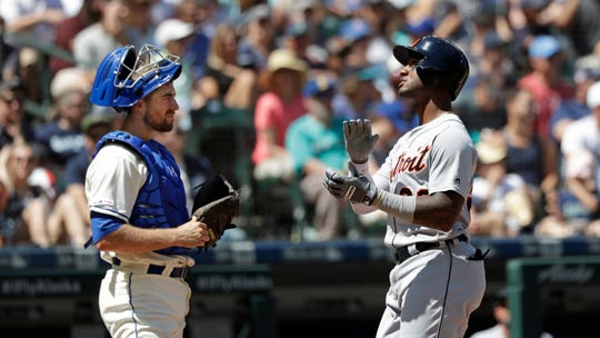 Tigers shortstop Niko Goodrum, right, claps his hands together as he crosses home on his solo home run in front of Mariners catcher Tom Murphy in the fourth inning on Sunday, July 28, 2019, in Seattle.