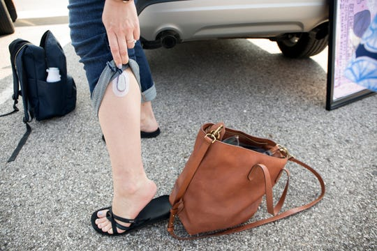 Stephanie Odette, 30, of Berkley shows reporters her continuous glucose monitor in Detroit on Sunday while waiting to board a bus to Canada to purchase insulin.