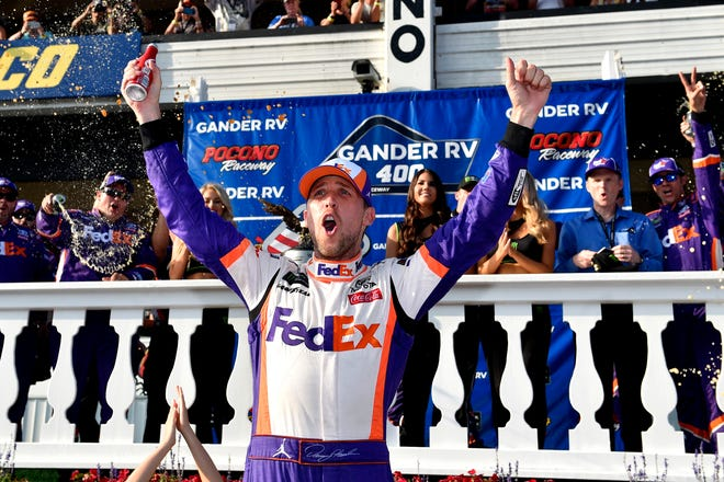 Denny Hamlin celebrates in Victory Lane after winning Sunday's NASCAR Cup Series race.