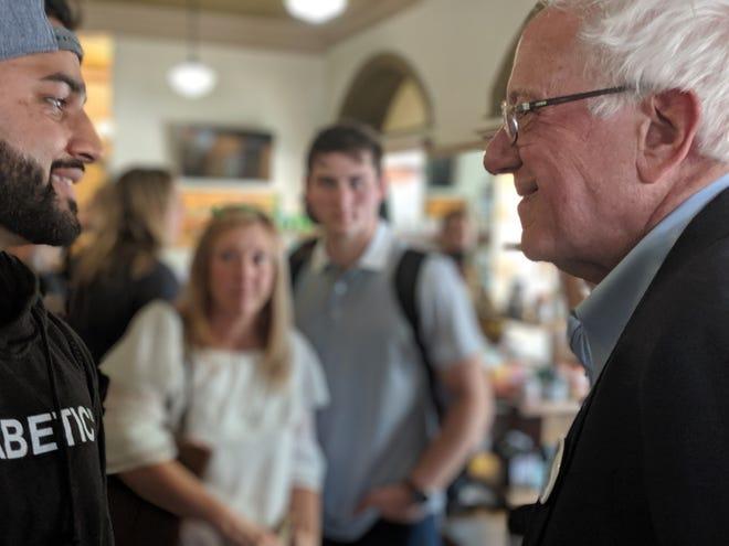 Bernie Sanders talks to Sahil Mehta of Novi on July 28, 2019, at The Olde Walkerville Pharmacy in Windsor, Ontario.