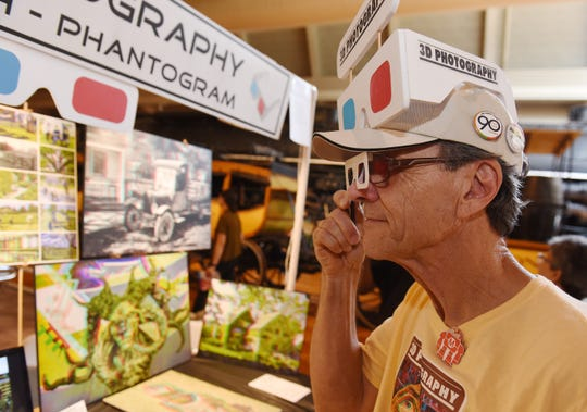 David Smith, 69, of Dearborn, owner of 3D Photography, looks through a pair of 3D glasses to view a photograph.