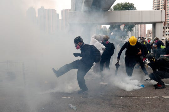 Protesters kick back and pick up tear gas canisters during a face off with riot police at Yuen Long district in Hong Kong Saturday, July 27, 2019. Police in Hong Kong shot tear gas at protesters who defied authorities' warnings not to march in a neighborhood where six days earlier a mob apparently targeting demonstrators brutally attacked people in a commuter rail station.