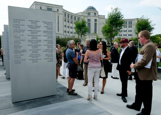 People gather around the sentinels with the names of law enforcement officers who have died in the line of duty at the Michigan Law Enforcement Officer's Memorial Monument Dedication and Memorial Service  on Saturday in Lansing.