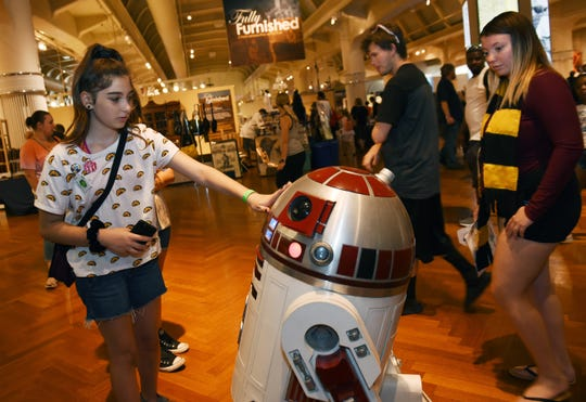 Alexis Ruffino, 12, of Port Huron, touches the R4-P23 droid robot, a replica of robots used in the 'Star Wars' movies. Maker Faire Detroit, the annual showcase of inventions and innovation at The Henry Ford, features demonstrations in everything from 3-D printing to blacksmithing to light-saber duels.