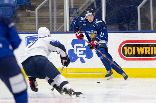 Red Wings draft choice Otto Kivenmaki, right, carries the puck against USA White at the World Junior Summer Showcase at USA Hockey Arena in Plymouth.