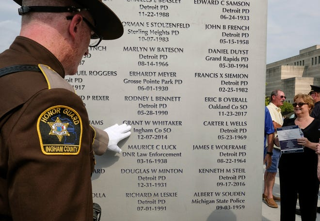 Ingham County Sheriff Deputy Matt Hutting touches the name of Grant W. Whitaker who died in the line of duty in December 2014 at the Michigan Law Enforcement Officer's Memorial Monument Dedication and Memorial Service Saturday in Lansing.