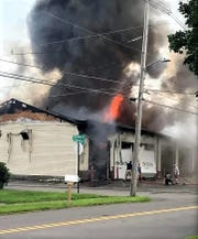 Flames shoot through the roof of the Lawrenceville Fire Department headquarters Saturday.