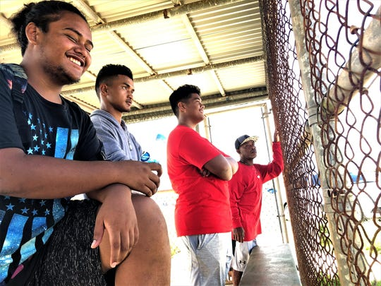 Spectators at the Kuchu Track and Field event watch from the nearby shade of a dugout. From left are Petrus Jack, 17, K.D. Choromay, 19, Brian Sam, 16 and Unisis Kayko, 53.