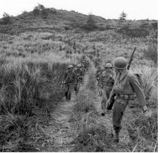 Army infantry on high ground above Agat keep their bayonets fixed for expected contact with Japanese soldiers. In late July 1944, CHamoru volunteers helped Army teams conduct reconnaissance southern Guam.