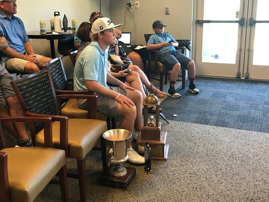 Nic Hofman sits among his trophies during the awards ceremony after the 2019 Lafayette Men's City Golf championship.