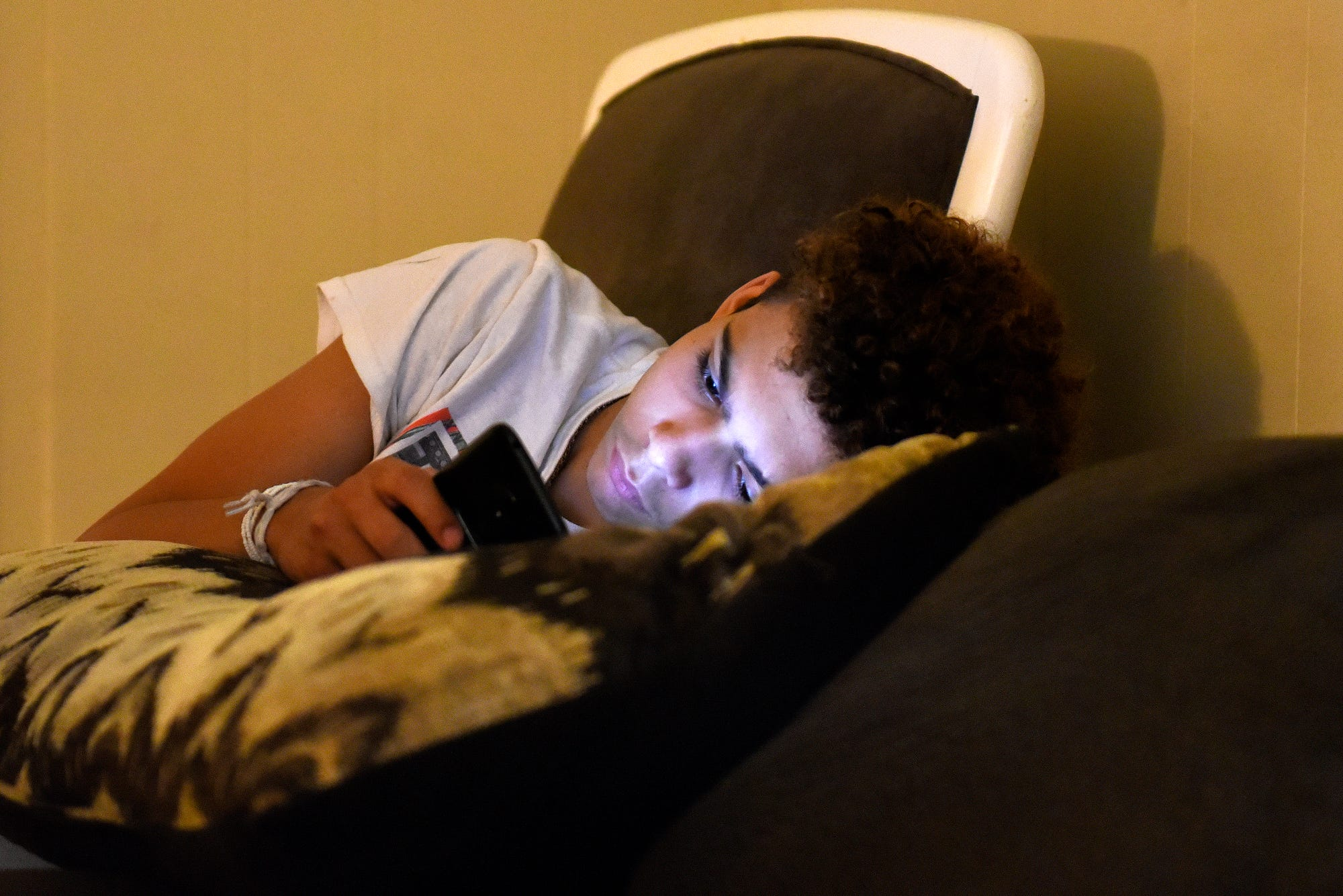 Lazarus Meissner looks at his phone while at home on Friday, July 26, 2019, in Lansing.