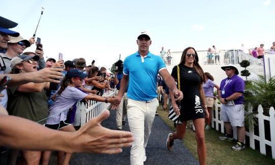 Brooks Koepka walks off No. 18 with girlfriend Jena Sims after winning the WGC-FedEx St. Jude Invitational on Sunday.