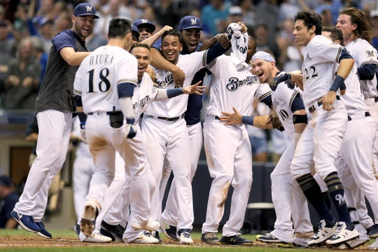 Keston Hiura  celebrates with teammates after hitting a home run to beat the  Cubs on Saturday night.
