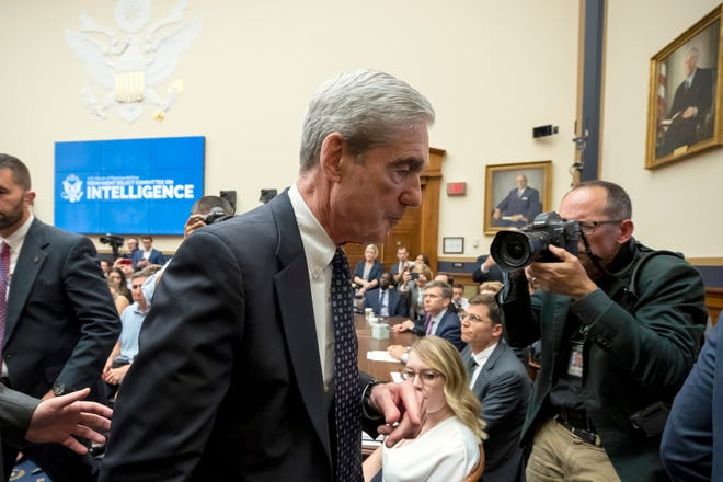 Former special counsel Robert Mueller, center, departs after testifying before the House Intelligence Committee hearing on his report on Russian election interference, on Capitol Hill, Wednesday, July 24, 2019 in Washington.