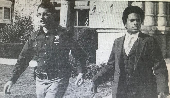 A deputy leads Theodore Burtley, then 19, from the Blackford County Courthouse on Oct. 29, 1982. after a jury found him guilty of murder and robbery in the shooting death of an employee at a Muncie furniture store. The case had been moved from Delaware to Blackford County.