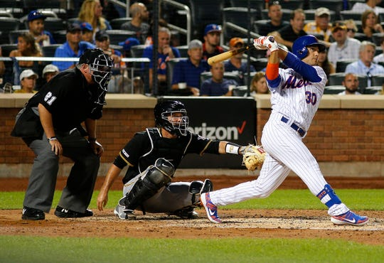 Jul 27, 2019; New York City, NY, USA; New York Mets center fielder Michael Conforto (30) hits a solo home run against the Pittsburgh Pirates during the sixth inning at Citi Field.