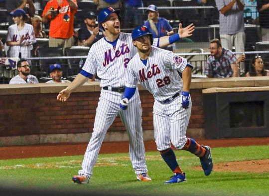 New York Mets' Todd Frazier (21) celebrates with teammate J.D. Davis (28) after they score on a two-run home run by Davis during the seventh inning of a baseball game against the Pittsburgh Pirates Saturday, July 27, 2019, in New York.