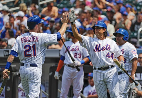 New York Mets' Todd Frazier (21) celebrates with Jason Vargas after scoring on an RBI-single by Amed Rosario during the first inning of a baseball game against the Pittsburgh Pirates, Sunday, July 28, 2019, in New York.