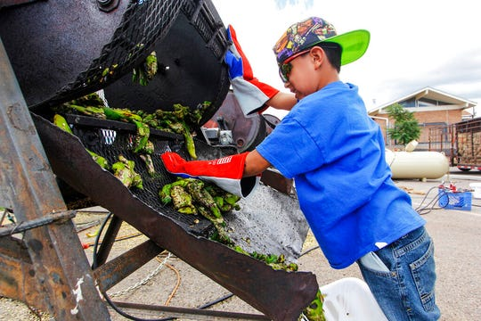 In this Aug. 9, 2017, file photo, Chris Duran Jr., 7 helps roast green chile with his family outside the Big Lots in Santa Fe. A hybrid version of a New Mexico chile plant has been selected to be grown in space as part of a NASA experiment, officials recently announced.