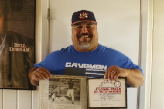 Carlsbad's Eric Chavez holds up an old Farmington Daily Press newspaper clipping from 1988 with him playing against Puerto Rico in the Connie Mack World Series.