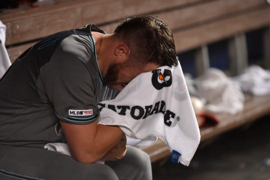 Greg Holland #56 of the Arizona Diamondbacks wipes his face with a towel after being pulled in the ninth inning against the Miami Marlins at Marlins Park on July 26, 2019 in Miami, Florida.