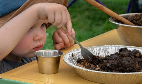 Two-year-old Luke Sells makes a mud pie at a children's table during the recent Old Fashioned Family Picnic sponsored by the Ma & Pa Railroad Heritage Village at Muddy Creek Forks.