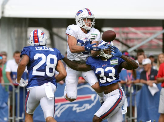 Bills receiver Nick Easley tries to go over defender Siran Neal and Kurt Coleman to make a catch during training camp.