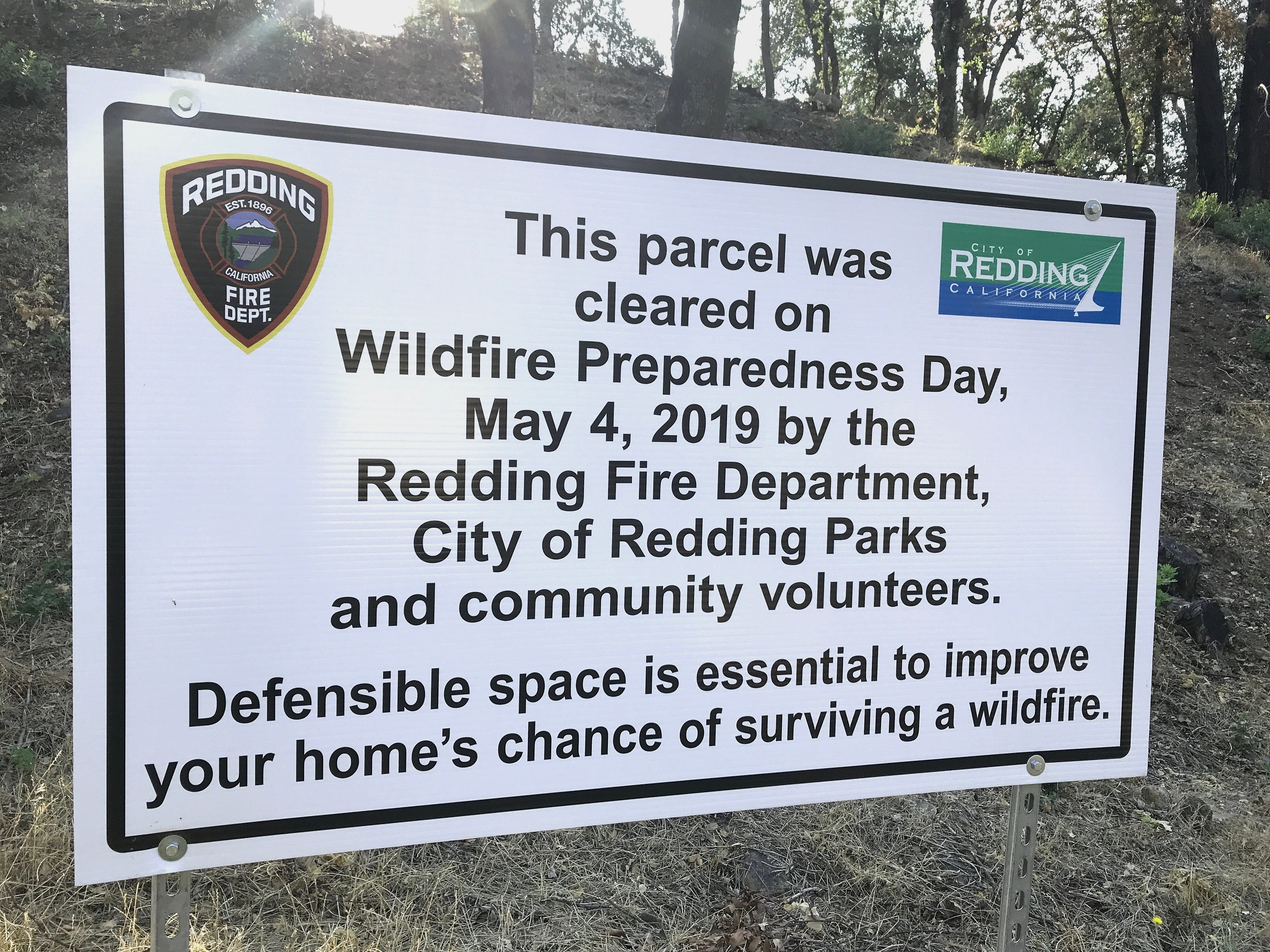 A Redding Fire Department sign on a hillside off Blazingwood Drive in Country Heights points out the defensible space work done in the spring. The other side of the street, however, remained uncleared months later.