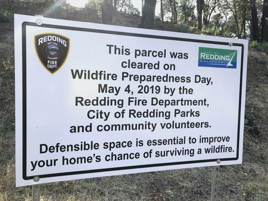 The Redding Fire Department put up this sign on a hillside off Blazingwood Drive in Country Heights pointing out the defensible space work that was done in the spring. The other side of the street, however, has a large brush pile that still needed to be cleared on July 27, 2019.