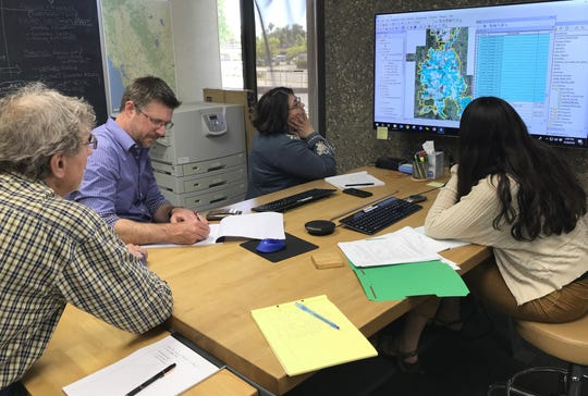 Examining ENPLAN's map of wildfire risk  factors are, from left to right, ENPLAN CEO Randall Hauser, Regional Executive Editor Silas Lyons and Local News Editor Jenny Espino, both of the Record Searchlight, and Catalina Llanos of ENPLAN.