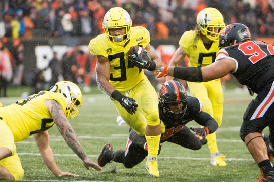 Nov 23, 2018; Corvallis, OR, USA; Oregon Ducks running back CJ Verdell (34) breaks away from Oregon State Beavers defenders for a touchdown during the second half at Reser Stadium. The Oregon Ducks beat the Oregon State Beavers 55-15. Mandatory Credit: Troy Wayrynen-USA TODAY Sports