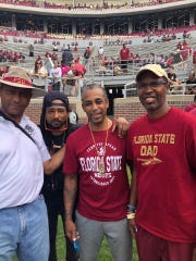 Former Seminoles, left to right, Hector Gray, Bobby Jackson, center, and Charlie Ward with Jackson's son.