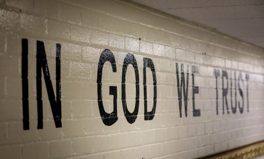 "This July 23, 2019 photo shows ""In God We Trust"" stenciled in a wall at South Park Elementary in Rapid City, S.D."