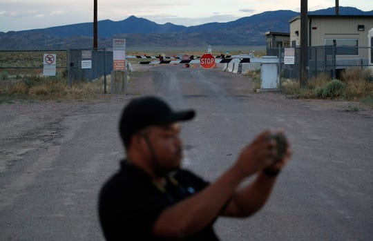 "In this July 22, 2019 photo, Terris Williams visits an entrance to the Nevada Test and Training Range near Area 51 outside of Rachel, Nev. The U.S. Air Force has warned people against participating in an internet joke suggesting a large crowd of people ""storm Area 51,"" the top-secret Cold War test site in the Nevada desert."