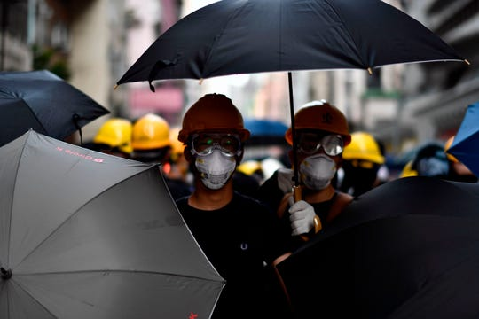 Protesters stand together with umbrellas as they face off with police during a demonstration against a controversial extradition bill in Hong Kong on July 28, 2019.