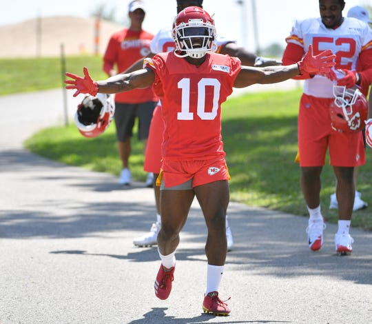 Kansas City Chiefs wide receiver Tyreek Hill (10) signals to fans as he walks to the field before training camp at Missouri Western State University.