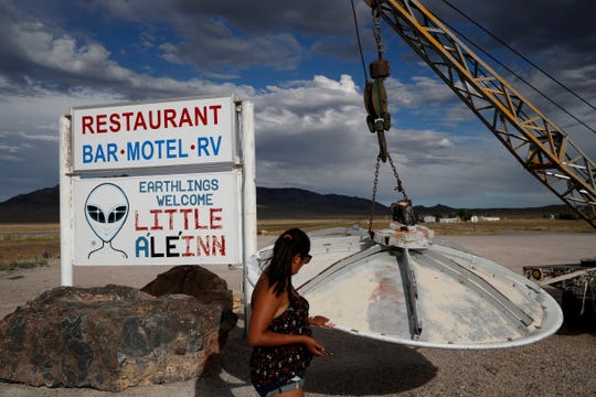 "In this July 22, 2019 photo, Grace Capati looks at a UFO display outside of the Little A'Le'Inn, in Rachel, Nev., the closest town to Area 51. The U.S. Air Force has warned people against participating in an internet joke suggesting a large crowd of people ""storm Area 51,"" the top-secret Cold War test site in the Nevada desert."
