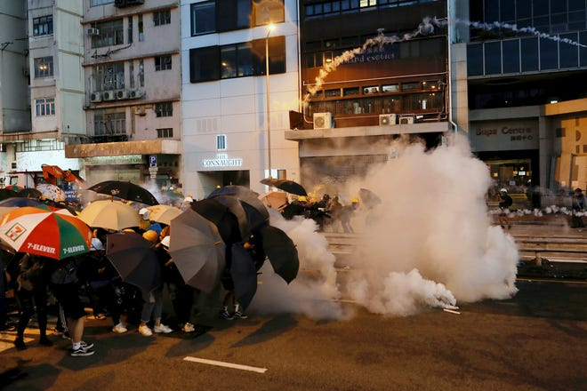 Protesters use umbrellas to shield themselves from tear gas fired by policemen as they face off on a streets in Hong Kong, Sunday, July 28, 2019. Police launched tear gas at protesters in Hong Kong on Sunday for the second night in a row in another escalation of weeks-long anti-government and pro-democracy protests in the semi-autonomous Chinese territory.