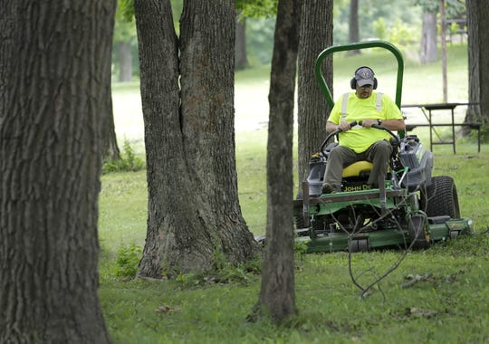 Sam Johnson cuts grass in a picnic area of High Cliff State Park Friday, July 26, 2019, in Sherwood, Wis.