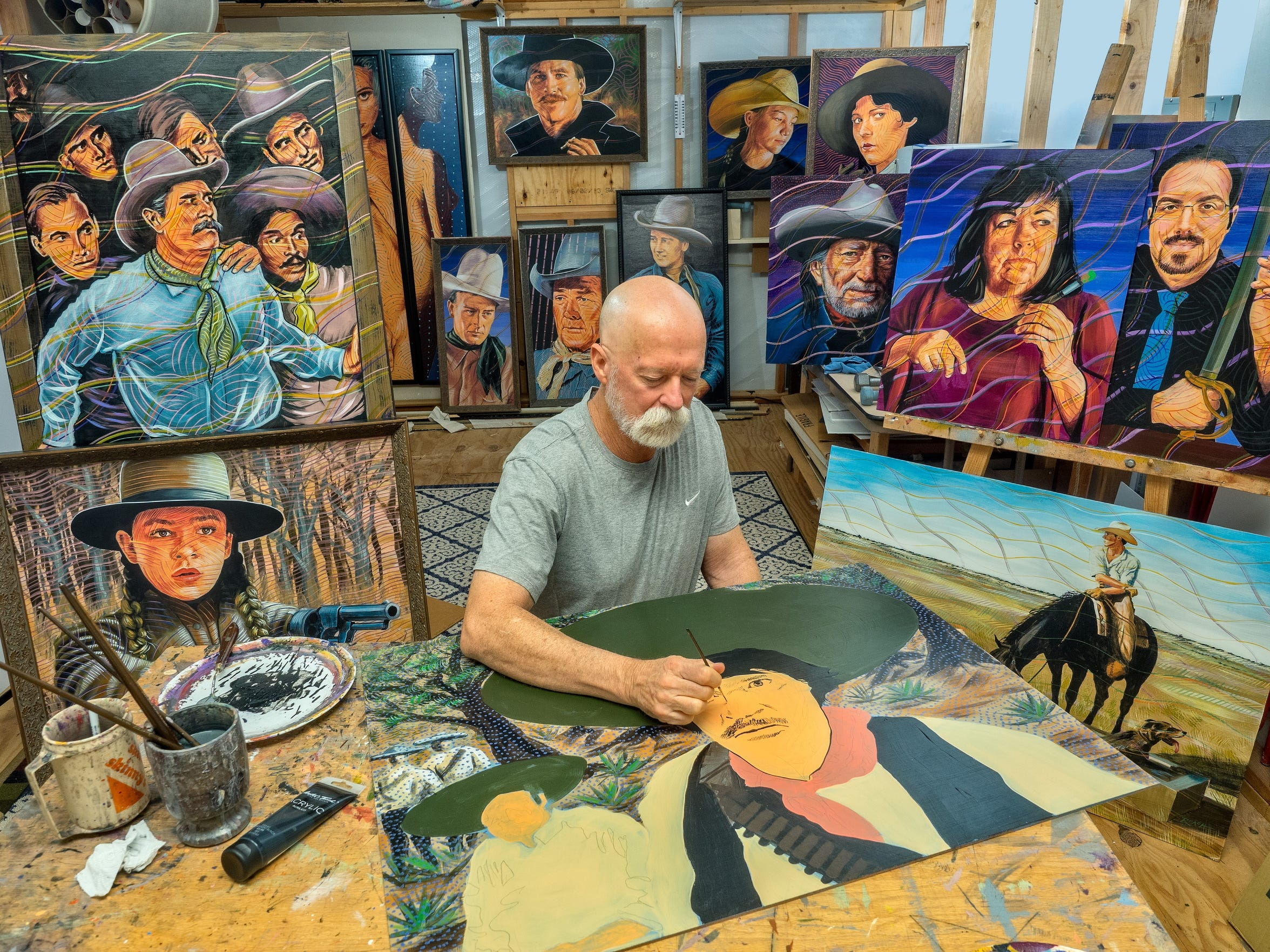 Don't put that paint brush down, a figure appears to be advising artist Chuck Roach, at work in his studio with others looking on.