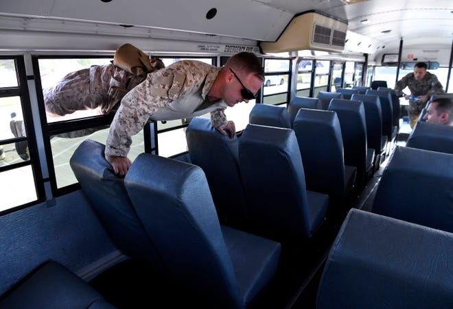 Marine Corps SSgt. Charles Valentine of the 1st. EOD Company from Marine Corps Base Camp Pendleton, California, crawls through a bus window during a to reach a hostage during a training exercise Thursday.