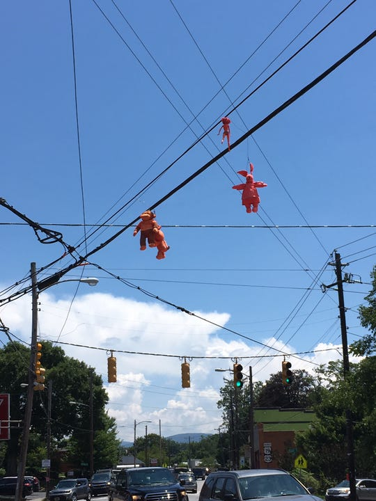 Someone has been hanging pink dolls on utility lines in West Asheville. Duke Energy removed this batch recently, even though they were on phone company lines.