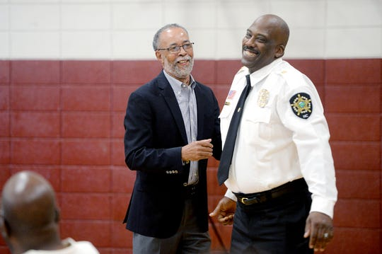 Asheville Housing Authority CEO Gene Bell jokes with Buncombe County Sheriff Quentin Miller at Bell's retirement party at the Arthur R. Edington Center on July 25, 2019. Bell retired after 25 years with the housing authority.