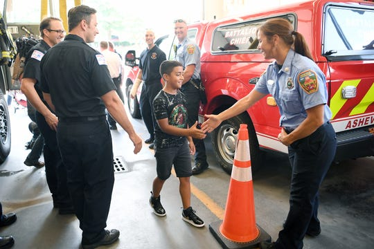 Jayden Castillo, 9, is welcomed into Asheville Fire Department Station 5 by public information officer Kelley Klope and other firefighters as he arrives for a ceremony in his honor on July 29, 2019. On June 30, 2019 Jayden's quick actions helped save the life of 5-year-old Marlee Shelton, 5, who he pulled from the bottom of a swimming pool.