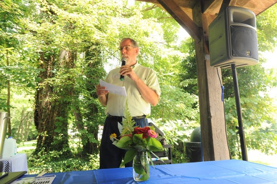 Brian McCartney the current chair of the High Top Colony board, welcomes around 100 people to the centennial celebration of the Black Mountain community on July 27.