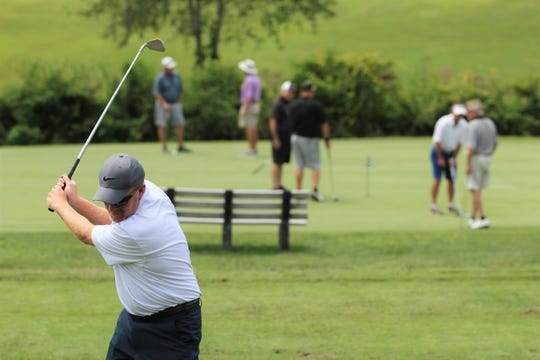 Golfers warm up before the 33rd annual Warhorse Classic at the Black Mountain Golf Course on July 27.
