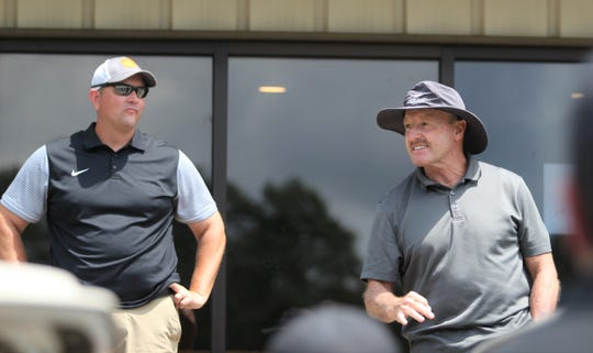 Kenny Ford, right, who coached the Owen Warhorse football team for 29 seasons, gives final instructions to golfers in the 33rd annual Warhorse Classic as current head coach Nathan Padgett looks on.