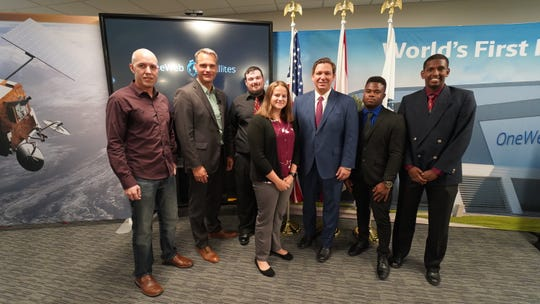 Kai Schmidt, Human Resources Director at OneWeb Satellites, and Florida Governor Ron DeSantis with a few of the apprentices selected for the program.