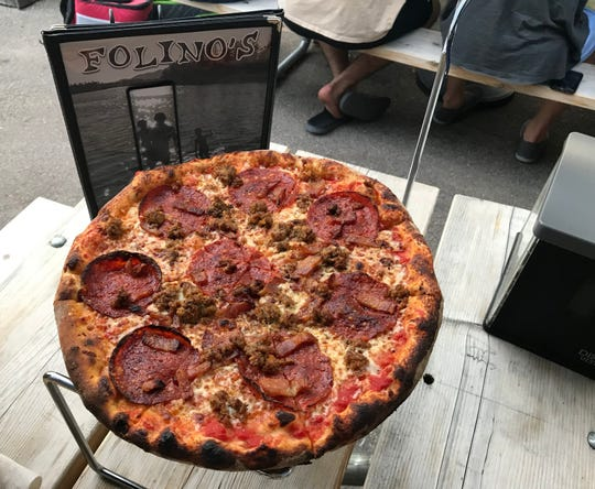 A small The Meats, tomato sauce base, mozzarella, pepperoni, house made sausage, bacon, graces a table at Folino's in Burlington on Saturday, July 27, 2019.