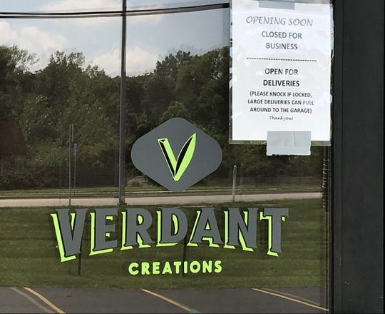 "A sign on the door at the door at the Verdant Creations medical marijuana dispensary in Columbia Township reads ""opening soon."""